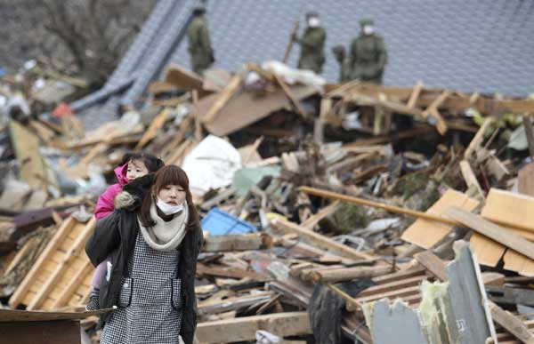 A woman carrying a girl on her back walks in a devastated area during a search operation in Ofunato, Iwate Prefecture, northern Japan, Tuesday, March 15, 2011, after a powerful earthquake-triggered tsunami hit the country&#39;s east coast on Friday.  <span class=meta>(&#40;AP Photo&#47;The Yomiuri Shimbun, Masamichi Genko&#41;)</span>
